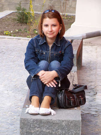 stilish: Casual girl sitting on a bench with sunglasses