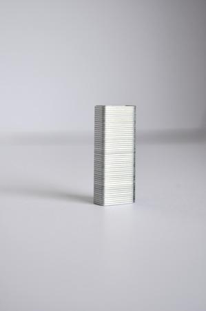 staples: Silver staples on gray background Stock Photo