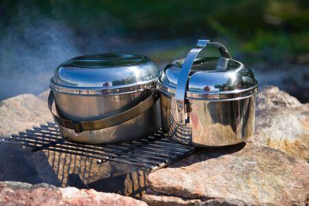 utensilios de cocina: Utensilios de cocina de camping brillante en un incendio Foto de archivo