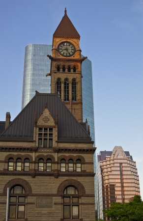 View of old historic Toronto city hall and the clock tower in front of the modern skyscraper at sunset photo