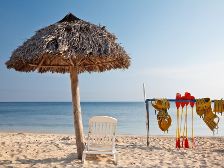 watersport: Caribbean tropical beach  with straw umbrella and watersport equipment Stock Photo