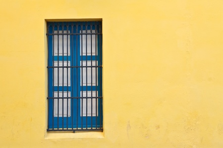 lattice window: Blue window and bright yellow wall in old city of Havana, Cuba