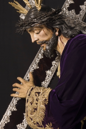tortured body: jesus with cross slope with gold-embroidered tunic