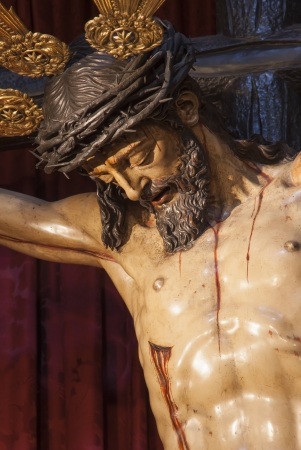 tortured body: Jesus crucified on the cross arborea red background Stock Photo