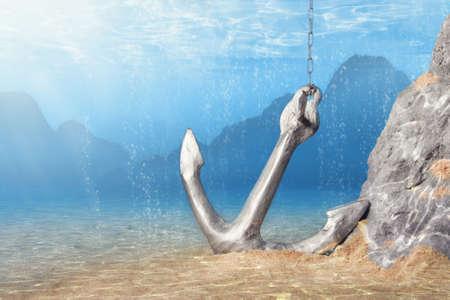 Foto van Anchor onderwater overspoeld met lichtstralen Stockfoto