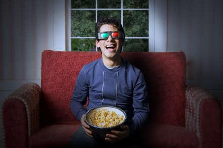 people watching tv: Adulto joven viendo una pel�cula 3d en el hogar