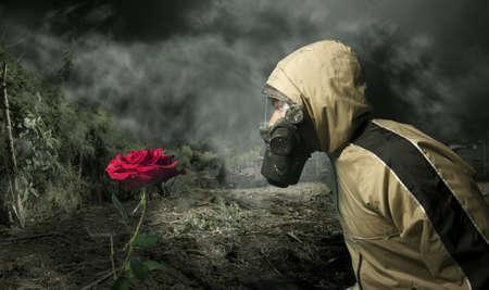 mascara de gas: Hombre de una máscara de gas mirando una rosa  Foto de archivo
