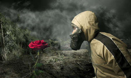 Homme dans un masque à gaz en regardant une rose