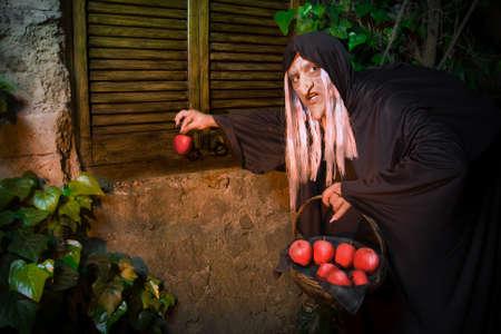bruja: Malvada bruja con manzana envenenada fuera de una casa