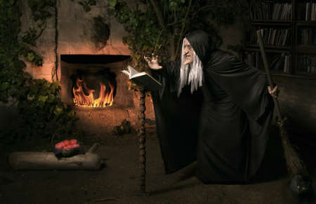 wicca: Halloween witch with her magic book casting a spell
