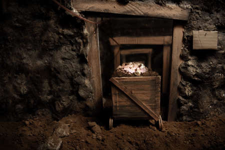 catacomb: Inside view in perspective of an old mine and trolley full of brilliant stones Stock Photo
