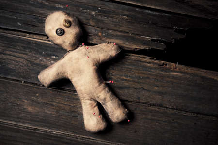 to curse: photo of creepy voodoo doll on wooden floor Stock Photo