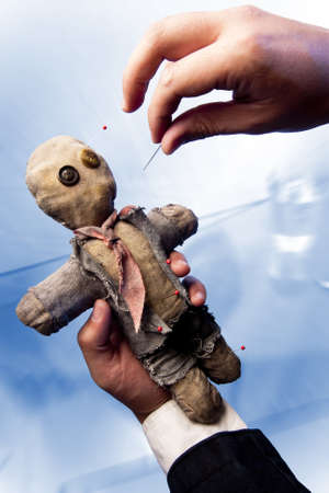 businessman making harm to coworker via voodoo photo