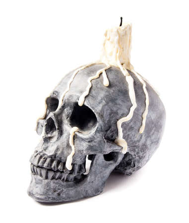 Halloween skull with candle melting on its head Stock Photo