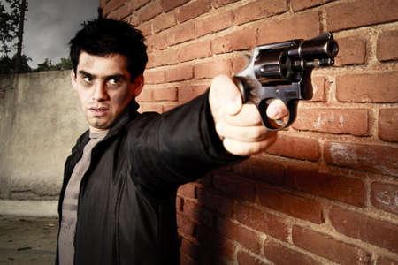 レンガの壁の他の銃を持つ男 写真素材