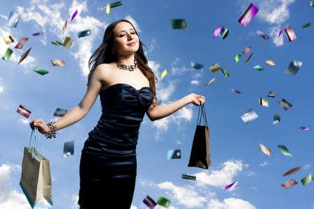 junge und schöne Frau mit Einkaufstüten und regnet Kreditkarten