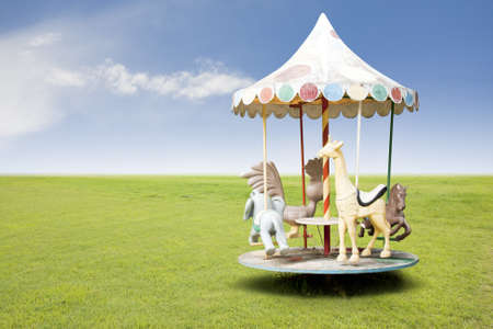circle shape: photo of a carousel for kids on grass field