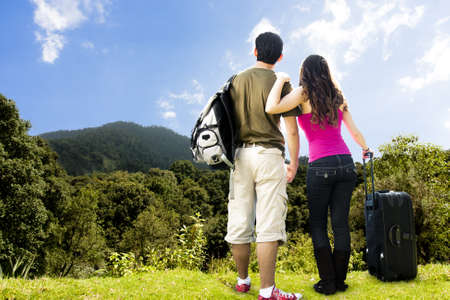 photo of beautiful Couple looking afar from the top of a mountain photo