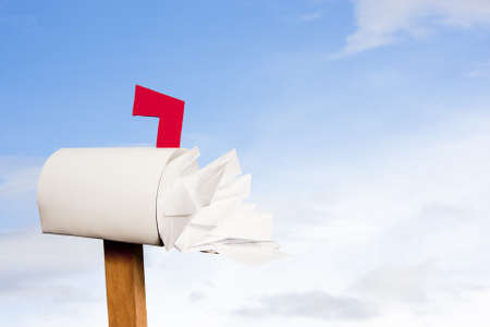 junk mail: Mail box overflowing with mail against sky
