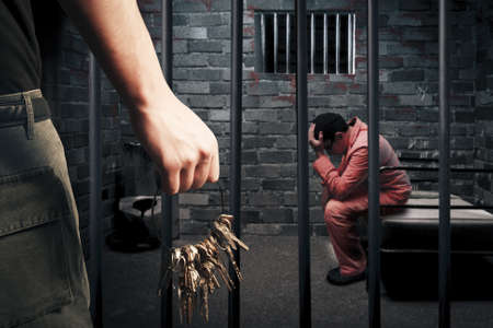 criminals: prison guard with keys outside dark prison cell Stock Photo
