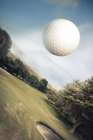 golf swings: Golf ball flying over green field Stock Photo
