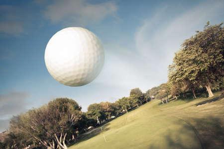 pelota de golf: Pelota de golf volando sobre el campo verde Foto de archivo