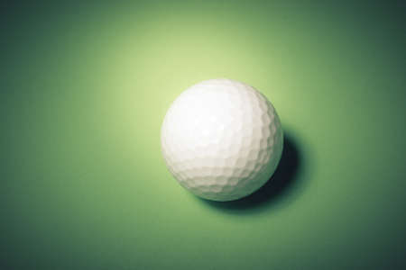 Golf ball over a green background photo