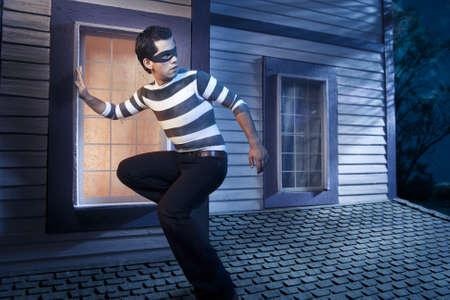 dangerous burglar about to enter house