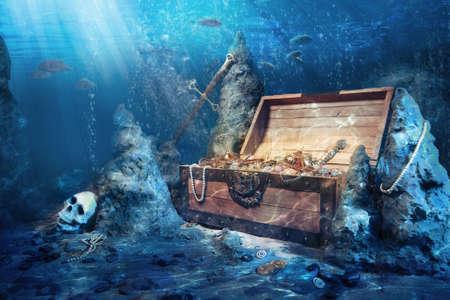 Foto van open schatkist met glimmend goud onder water