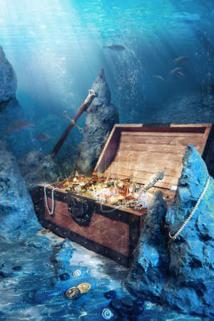 photo of open treasure chest with shinny gold underwater Stockfoto
