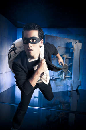 burglar protection: thief running out of a bank vault, low-key photo