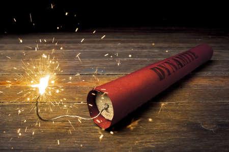 dinamita: Cartucho de dinamita encendido en la madera