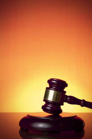 オレンジ色の背景上の裁判官の小槌 写真素材