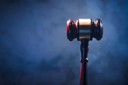 judge gavel on blue background with smoke and dramatic lighting photo