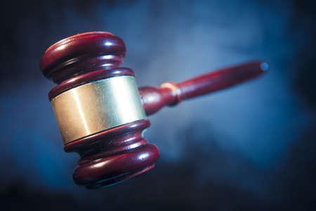 judge gavel on blue background with smoke and dramatic lighting photo