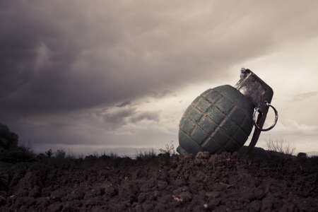 green grenade resting on a battlefield photo
