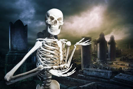 headstone: human skeleton in a graveyard at Halloween Stock Photo