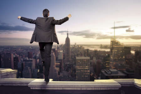 Troubled businessman jumping from the top of a building photo