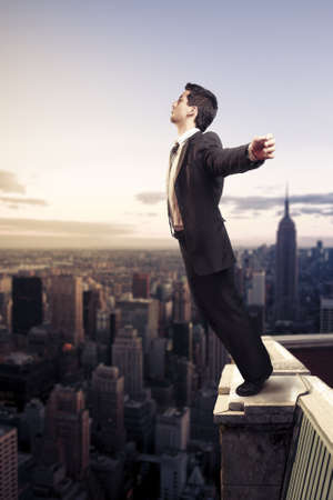 edge: Troubled businessman letting go from the top of a building