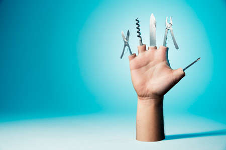 business survival: Open hand with tools on a blue background Stock Photo