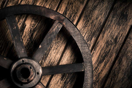 country western: Dramatic lighting on a wood wheel on a grungy background