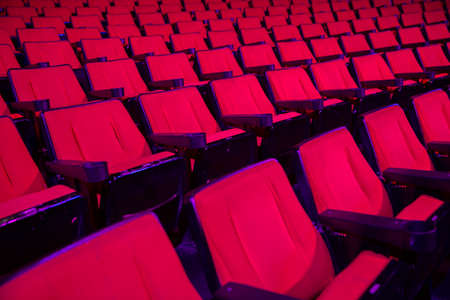 Empty rows of red theater or movie seats photo