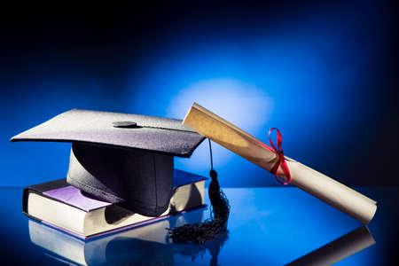 Diploma, Afstuderen hoed en boek op een blauwe achtergrond Stockfoto
