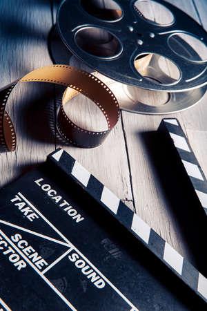 Film klepel en film reel op een houten backgorund Stockfoto