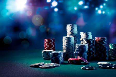 Poker Chips op een speeltafel met dramatische verlichting Stockfoto