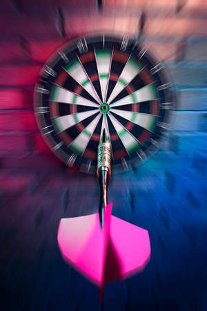 score board: dartboard on a brick wall about to get hit by dart