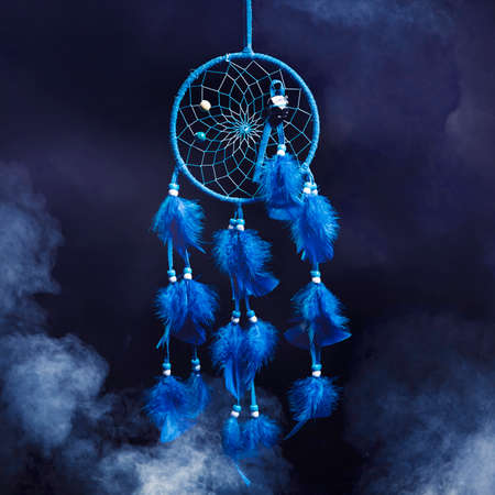 Dreamcatcher with smoke on a dark background photo