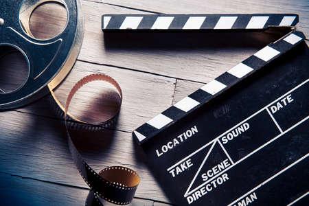 carrete de cine: Chapaleta de la pel�cula y rollo de pel�cula en un backgorund madera