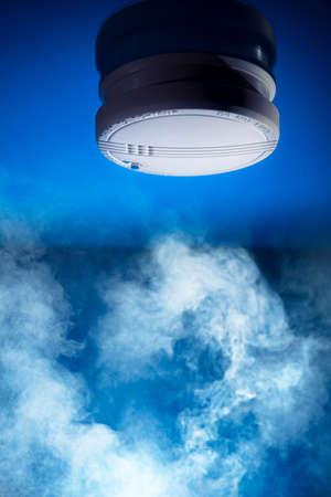 humo: detector de humo sobre un fondo azul Foto de archivo