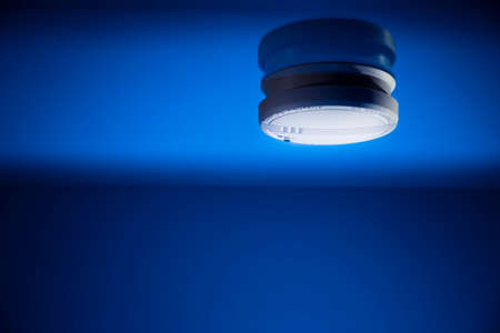 smoke detector on a blue background Stock Photo